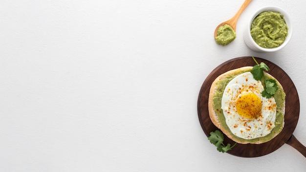 Pita piatta con crema di avocado e uovo fritto con copia-spazio Foto Gratuite