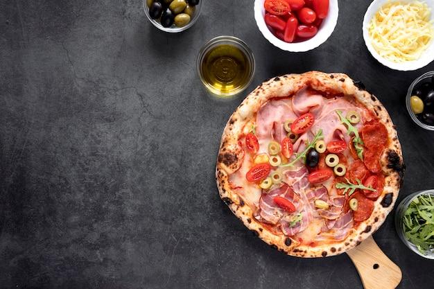 フラットレイアウトのピザとトッピングの配置 無料写真