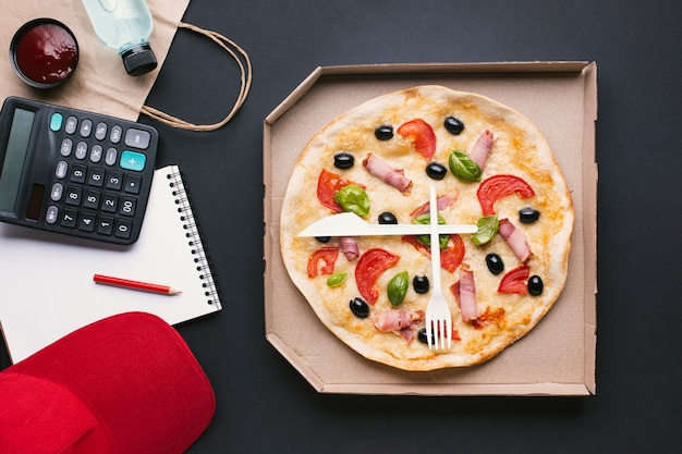 Flat lay pizza in a box with calculator Free Photo