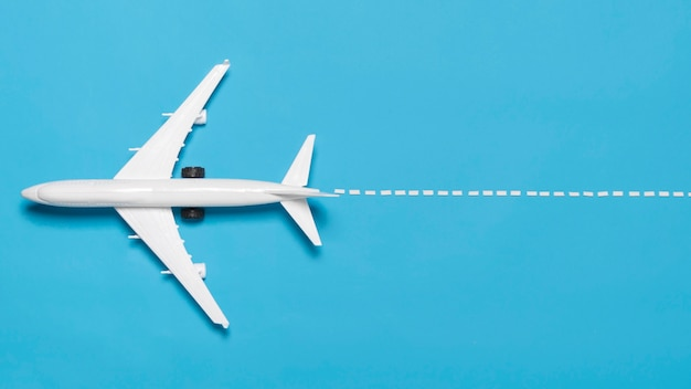 Flat lay plane on blue background Free Photo
