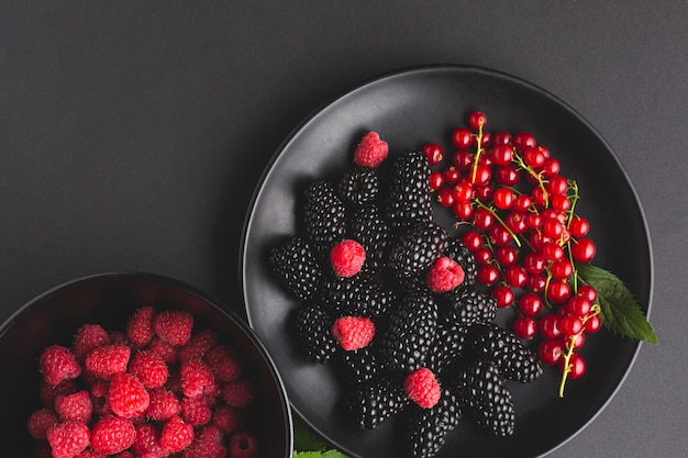 Flat-lay plate and bowl of fresh berries Free Photo