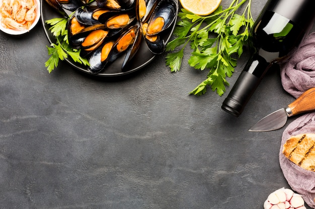 Flat-lay plate of cooked mussels and wine with copyspace Free Photo