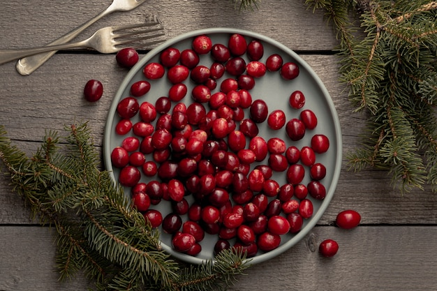 Flat lay of plate of cranberries with pine and forks Free Photo