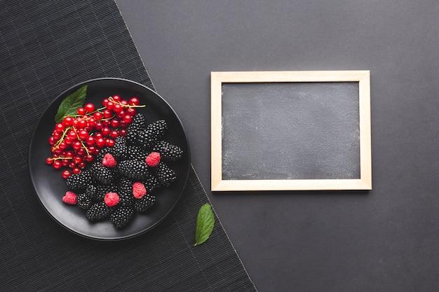 Flat-lay plate of fresh berries with blackboard Free Photo