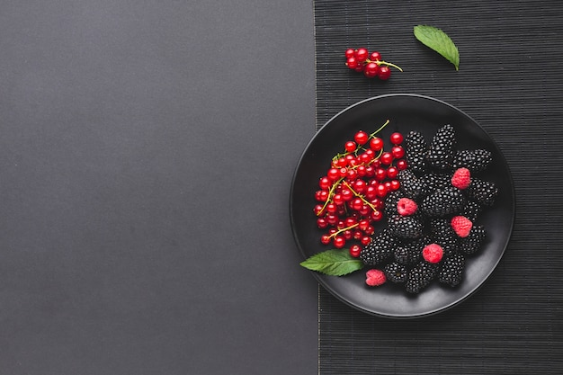 Flat-lay plate of fresh berries with copyspace Premium Photo