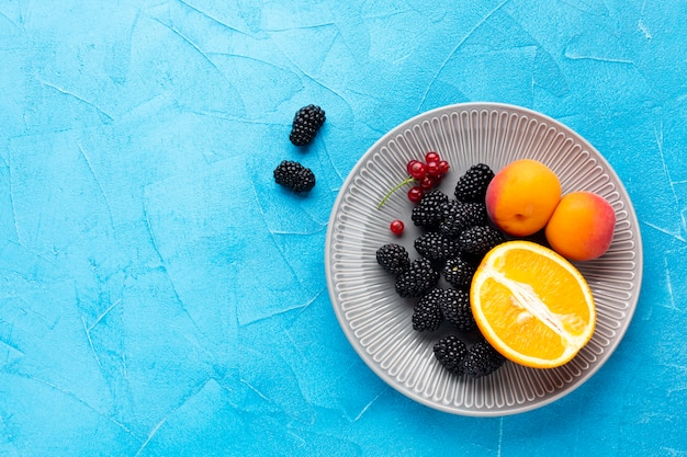 Flat-lay plate of fruits and berries with copyspace Free Photo