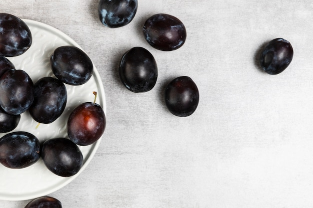 Flat lay of plums in plate on wooden background Free Photo