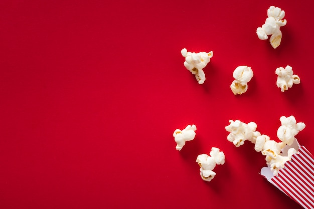Flat lay popcorn on red background with copy space Free Photo