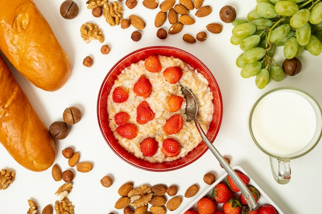 Flat lay porridge with fruits and nuts arrangement on plain background Free Photo