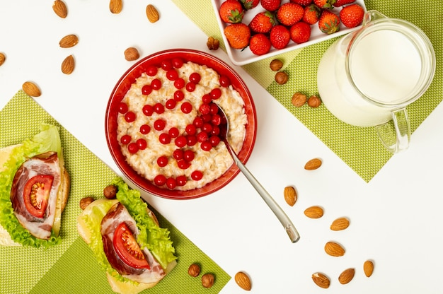 Flat lay porridge with fruits and sandwiches on plain background Free Photo