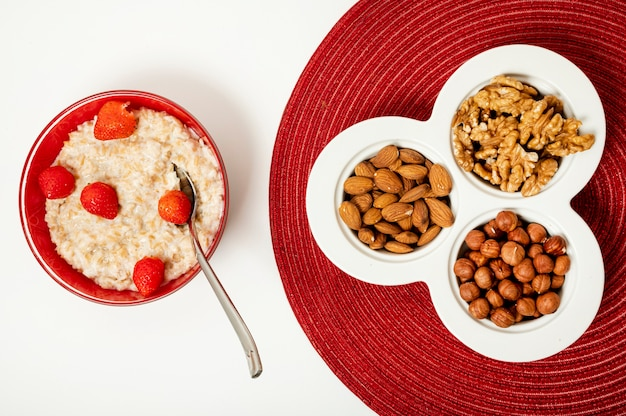 Flat lay porridge with nuts on plain background Free Photo