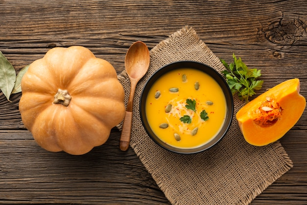 Flat lay pumpkin soup in bowl with pumpkin Free Photo