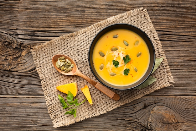 Flat lay pumpkin soup in bowl with wooden spoon Free Photo