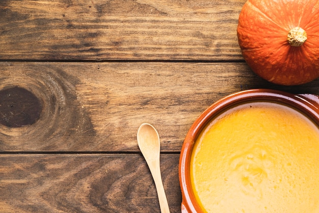 Flat lay pumpkin with soup and wooden spoon Free Photo