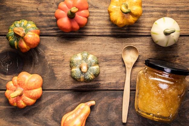 Flat lay pumpkins arrangement  with jam jar and spoon Free Photo
