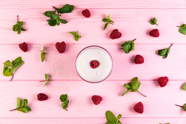 Flat lay raspberry milkshake on a pink wooden table Free Photo