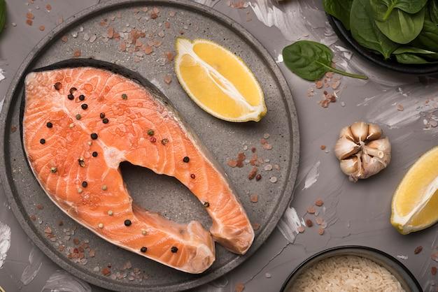 Плоский сырой стейк из лосося на подносе с ингредиентами Бесплатные Фотографии