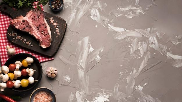 Плоский сырой стейк на косточке с вегетарианскими шампурами Бесплатные Фотографии