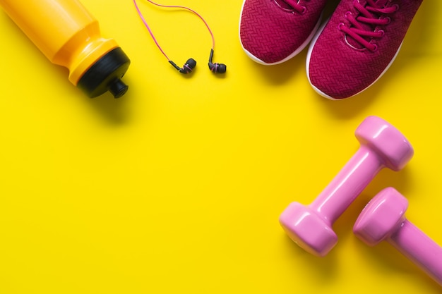 Flat lay of red sport shoes, pink dumbbells, earphones, bottle of water on yellow  backgro Premium Photo
