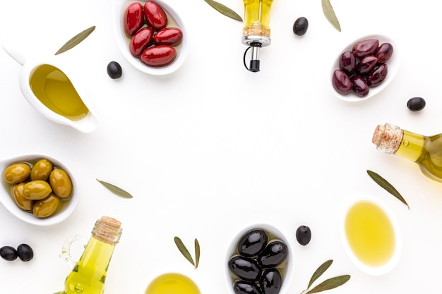 Flat lay red yellow black olives in spoons with oil bottles and copy space Free Photo