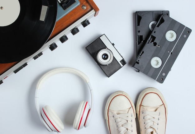 Плоские лежали объекты поп-культуры в стиле ретро 80-х. виниловый проигрыватель, наушники, видеокассеты, пленочная камера, кроссовки на белом фоне. вид сверху Premium Фотографии