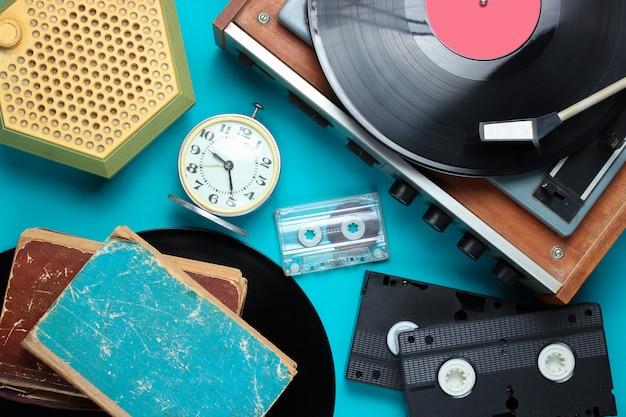 フラットレイアウトのレトロなスタイルの属性、80年代のメディア。ビニールプレーヤー、ビデオカセット、オーディオカセット、レコード、ラジオ、ビンテージの目覚まし時計、青の背景に古い本。 Premium写真