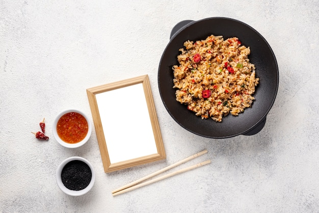 Flat lay rice and vegetables on plate with chopsticks with blank frame Free Photo