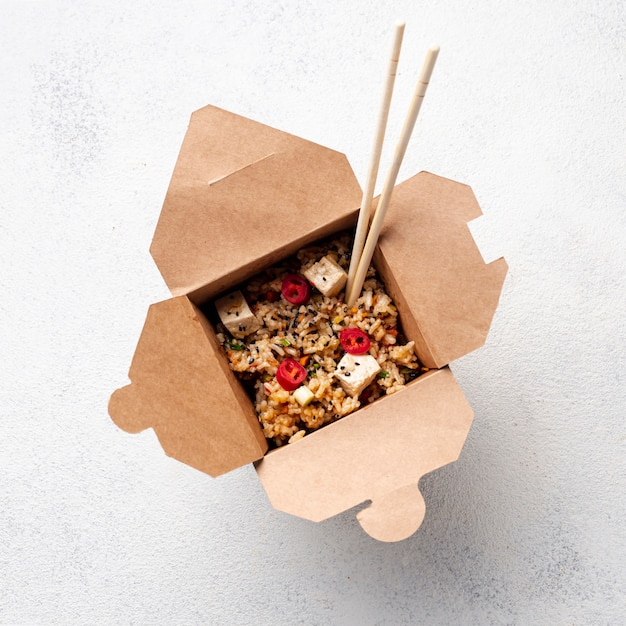 Flat lay rice and vegetables takeaway with chopsticks Free Photo