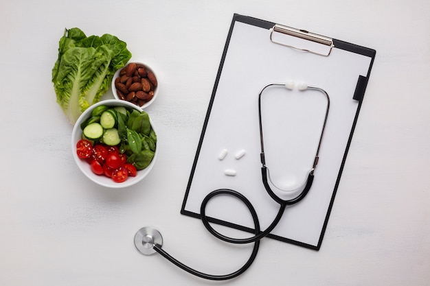 Flat lay of salad bowl and stethoscope Free Photo