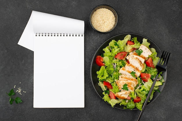 鶏肉とゴマのフラットレイサラダと白紙のノート 無料写真