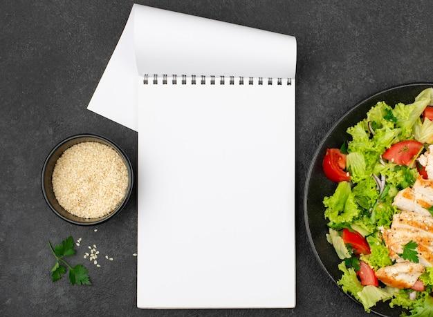 Плоский салат с курицей и кунжутом с пустым блокнотом Бесплатные Фотографии