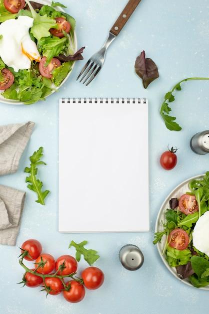 Плоский салат с жареным яйцом и помидорами с пустой записной книжкой Бесплатные Фотографии