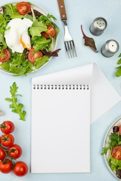 Плоский салат с жареным яйцом и помидорами с пустым блокнотом Бесплатные Фотографии