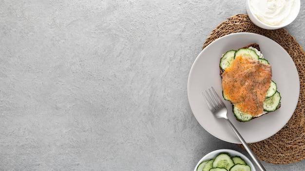 Panino piatto con cetrioli e salmone sulla piastra con copia-spazio Foto Gratuite