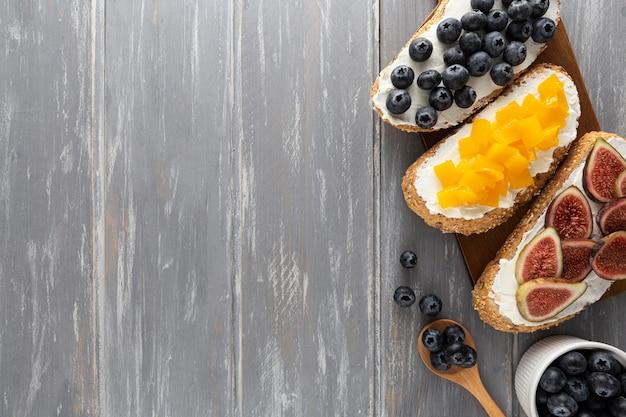 Panini piatti con crema di formaggio e frutta con copia-spazio Foto Gratuite