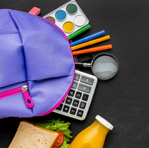 Flat lay of school essentials with backpack and calculator Free Photo