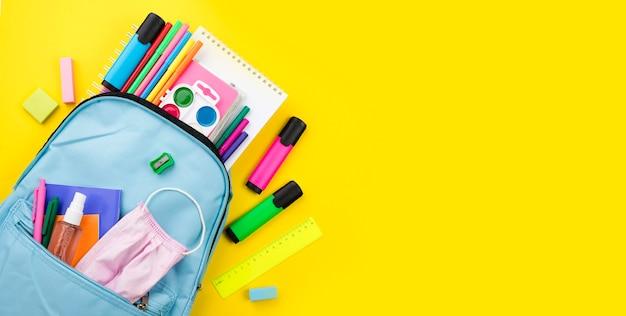 Disposizione piana degli elementi essenziali della scuola con lo zaino e le matite colorate Foto Gratuite