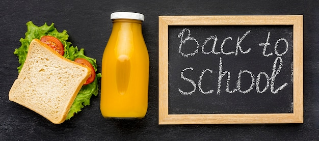 Flat lay of school essentials with blackboard and lunch Free Photo