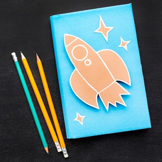 Disposizione piana degli elementi essenziali della scuola con il libro e le matite Foto Gratuite
