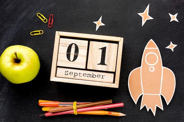 Disposizione piana degli elementi essenziali della scuola con calendario e mela Foto Gratuite