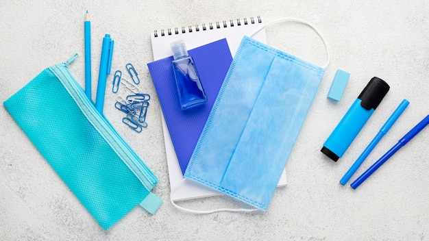 Flat lay of school essentials with notebook and medical mask Free Photo