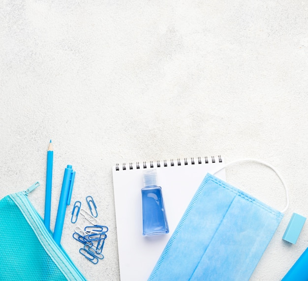 Flat lay of school essentials with paper clips and medical mask Free Photo