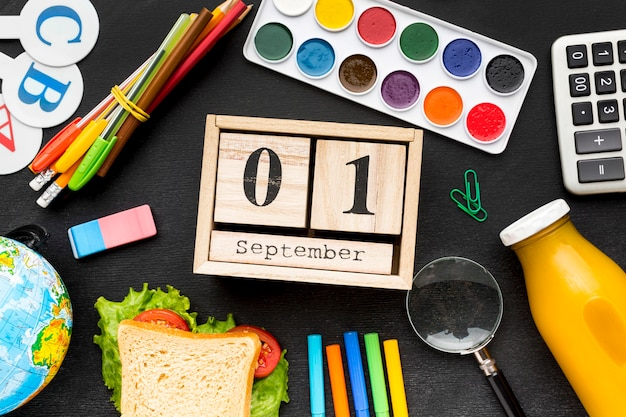 Flat lay of school essentials with sandwich and calendar Free Photo