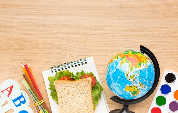 Flat lay of school essentials with sandwich and globe Free Photo
