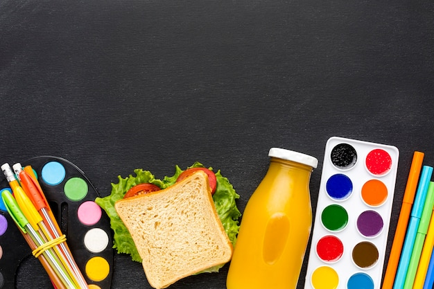 Flat lay of school essentials with sandwich and juice Free Photo