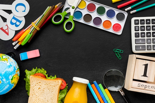 Flat lay of school essentials with sandwich and watercolor Free Photo