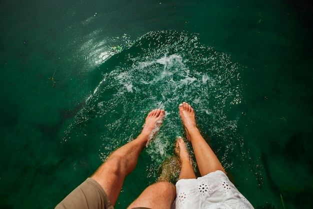 Flat lay shot of couple playing in the water with their feet Free Photo