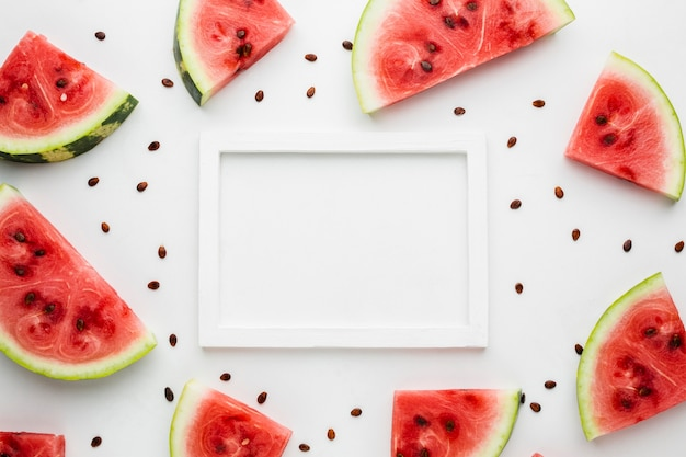 Flat lay sliced watermelon on white background with frame Free Photo