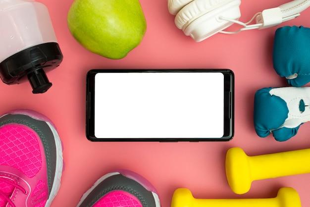 Posa piatta dello smartphone con elementi sportivi essenziali Foto Gratuite