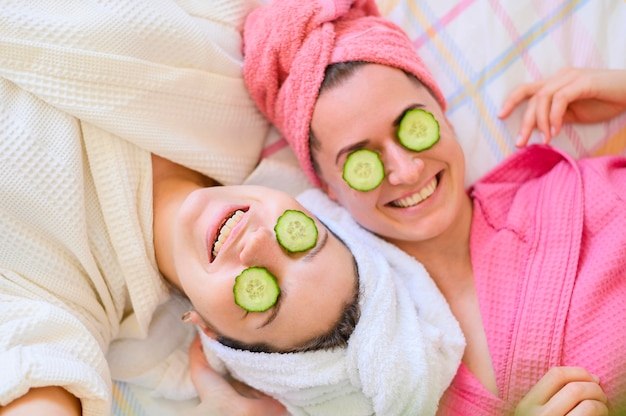 Flat lay of smiley women with cucumber slices on eyes Free Photo
